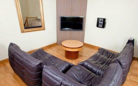 Aménagement d'un angle de mur, qui offre du rangement pour les dvd, le matériel électronique et la pose de la télé. Réalisation en stratifié Chêne goujé.