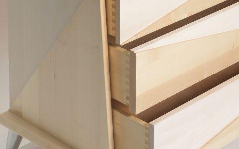 """Création du 20/07/15 : Commode Géométrique. Il s'agit d'une commode en Tilleul, composée de 3 tiroirs s'ouvrant avec un système pousse-lâche (une pression suffit à ouvrir le tiroir puis, inversement, à le refermer). Dimensions : 1250 x 800 de haut x 600 de profondeur. Les côtés de forme trapézoïdale sont composés de 2 triangles en reliefs, et les façades de tiroirs offrent la même caractéristique. Ces deux triangles sont aussi rappelés sur le dessus de la commode, mais sans le relief pour des raisons évidentes d'utilité. Finition : couleur naturelle/teinte blanche (alternées dans les triangles). L'ensemble: vernis ultra mat. Cette ligne simple et """"amusante"""" (suivant l'angle sous lequel on se place la commode est """"déformée"""") m'inspire, car l'on peut facilement la décliner en lit, en tête de lit, en chevet, ou en faire un petit bahut de salle à manger."""