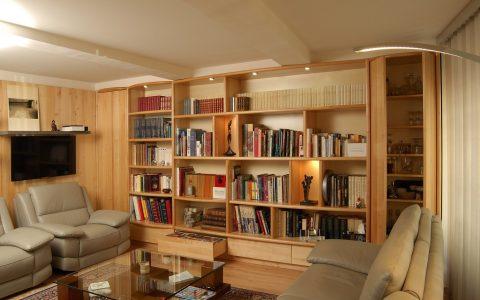 Superbe bibliothèque en Tilleul, deux corps de largeurs différentes. Tiroirs en partie basse, niches lumineuses, portes sur les deux côtés, éclairage par des spots. A gauche un panneau mural sur lequel sont fixés la télévision et des étagères.