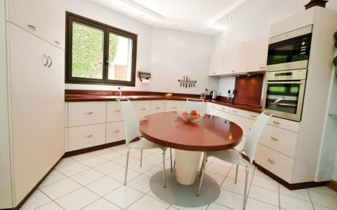Cuisine contemporaine utilisant des matériaux de très grande qualité: le plan de travail et les vasques intégrées sont en Corian, les portes et les façades de tiroirs sont en stratifié gougé, les tiroirs et les poignées sont en Inox.