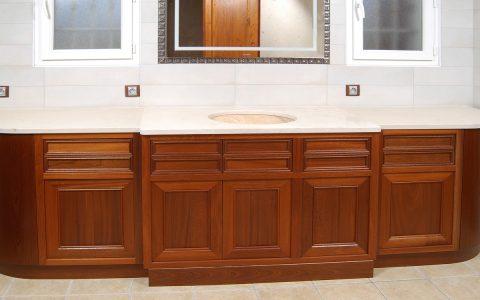 Grand meuble de salle de bains en Acajou d'inspiration Louis-Philippe offrant plusieurs rangements, ainsi que deux corbeilles à linge (partie cintrées ). Finition vernie.